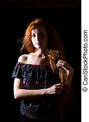 Dramatic portrait of sad red haired model on a dark background