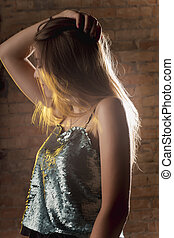 Dramatic portrait of young brunette model in the dark room