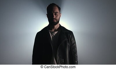 Dramatic portrait of young european man with beard in leather jacket looking at camera. Dark smoke studio or stage. Backlight, bright spotlight on background