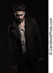 dramatic pose of a young fashion man with beard