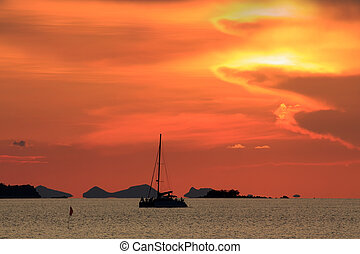 Dramatic red sunset sky and tropical sea image with yatch