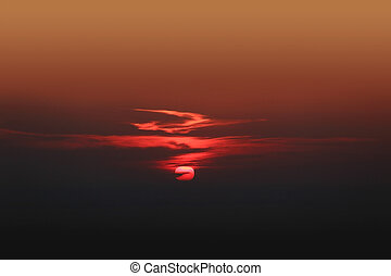 Dramatic red sunset with center sun and dark clouds