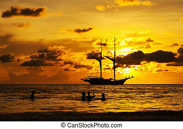 Dramatic sea and transport boat in color of sunset