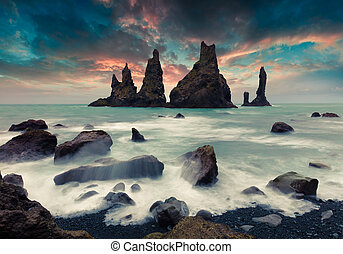Dramatic seascape of Reynisdrangar cliffs in the Atlantic ocean.