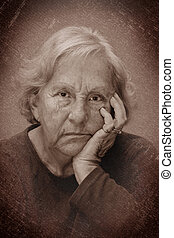 Dramatic grungy noisy almost black and white portrait of a real senior woman sulking, looking at camera.
