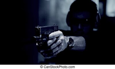 Dramatic shot of man shooting a gun - pistol shooting indoor