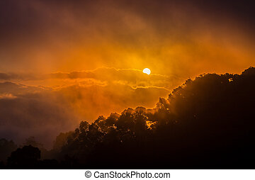 Dramatic sky of sunrise covered by cloud and fog