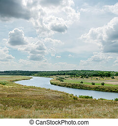 dramatic sky over green landscape with river