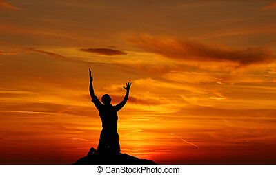 Silhouette of a man praying at sunset concept of religion