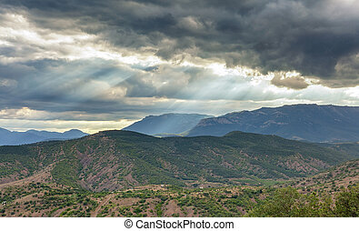 Dramatic stormy sky with sun rays through the clouds over a hilly valley with mountains in the distance