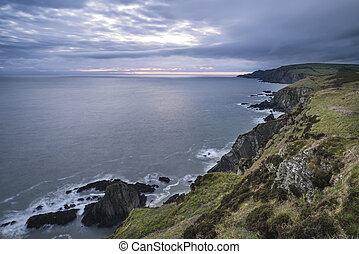Dramatic stormy sunrise landscape over Bull Point in Devon England