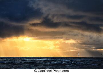 dramatic stormy sunset over sea horizon