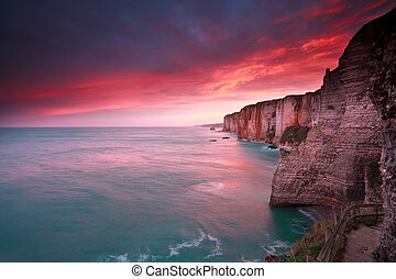 dramatic sunrise over ocean and cliffs