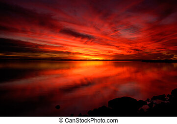 A fiery red sunset reflected in a lake.