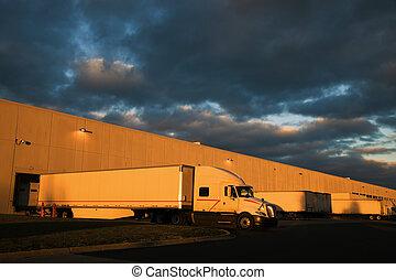 Dramatic sunset above distribution warehouse. Semi Truck...