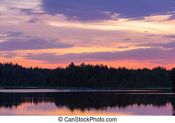 dramatic sunset over a forest lake