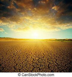 dramatic sunset over cracked desert