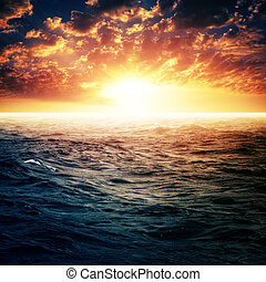 Dramatic sunset over ocean surface, abstract summer vacation backgrounds