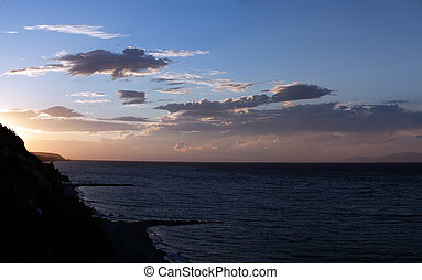Peloponnese, Greece - Dramatic sunset over the sea. ...