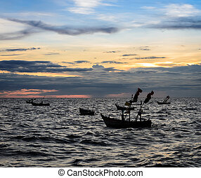 Dramatic sunset sky on the sea with fishing boat