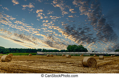 Dramatic sunset sky over hay field in the Kempen area, Belgium