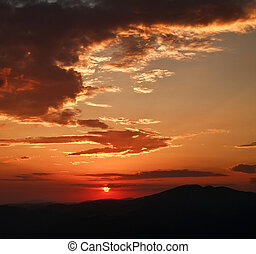 Dramatic sunset with clouds, in mountains, nature background