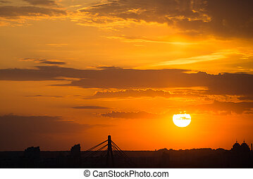 Dramatic sunset with orange sky and dark silhouettes of buildings