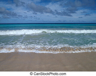 Dramatic wave sweeping away as another comes forward on a beach in Oahu, Hawaii with clouds in the sky. Pacific Ocean background.