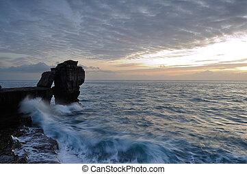 Dramatic winter sunset Pulpit Rock Portland Dorset.