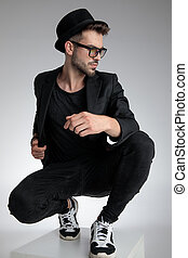 dramatic young man holding elbow in a fashion pose