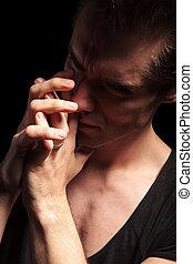 dramatic young man praying in studio