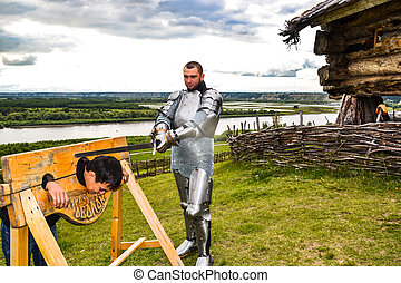 Dramatization penalty in the middle ages. Knight swung his sword at the prisoner.