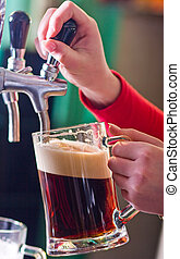 draught beer - glass being filled with draft beer by barman