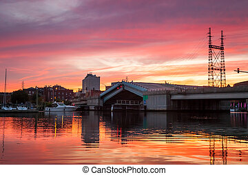 A drawbridge rising up for a boat to pass under a pink and orange sunset.
