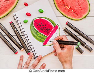 drawing a bright watermelon sketch with markers on wooden background