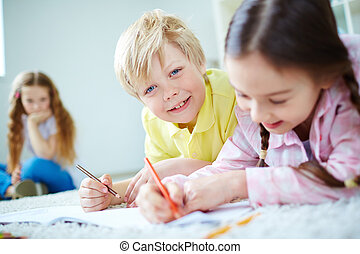 Drawing at leisure - Cute little boy looking at camera while...