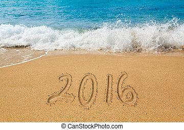 Drawing in sand by ocean of 2016 word