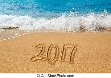 Drawing in sand by ocean of 2017 word