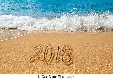Drawing in sand by ocean of 2018 word