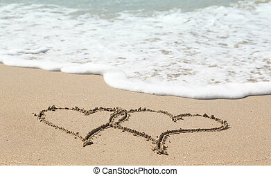 Drawing in sand by ocean of two hearts