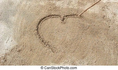 drawing in the sand - someone using a stick to draw in the...