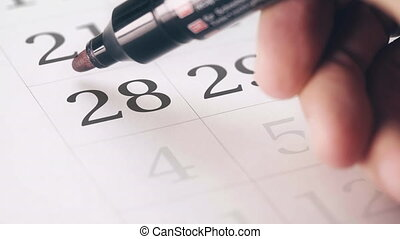 Drawing red circled mark on the twenty-eighth 28 day of a...