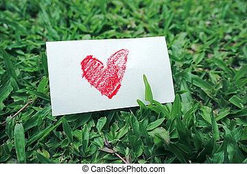 drawing red heart shape paper on green grass