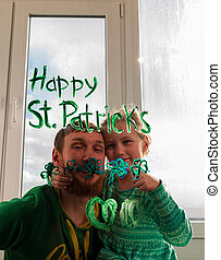 Drawing St. Patrick's Day Father with daughter painting green three-leaved shamrocks indoor, festive home decoration,family leisure. Drawing clover leaves on window glass. Stay home concept New normal
