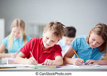 Drawing together - Portrait of two diligent pupils drawing...