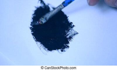Drawing with a brush on white paper with black oil paint