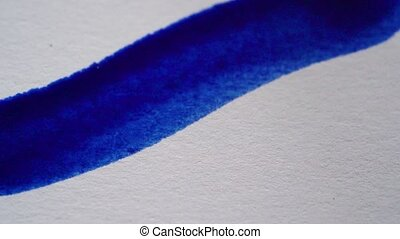 Drawing with a paintbrush on white paper with blue...