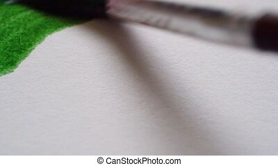Drawing with a paintbrush on white paper with green...