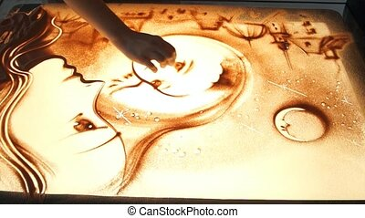 Drawing with sand. Drawing sand on a white screen. Sand...