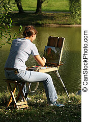 The woman draws paints on a coast of lake